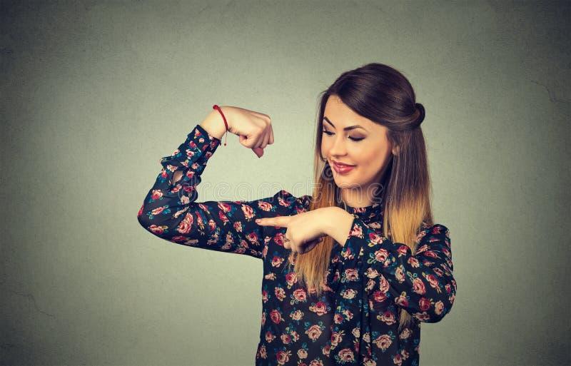 Mujer modelo sana joven apta que dobla los músculos que le muestran fuerza imagenes de archivo