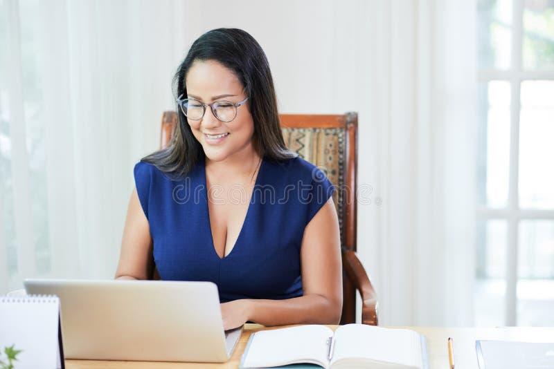 Mujer moderna adulta que trabaja en el ordenador portátil en oficina imagenes de archivo
