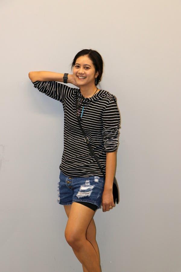 Mujer moderna asiática en blanco y color de las rayas negras de la camiseta de manga larga imágenes de archivo libres de regalías
