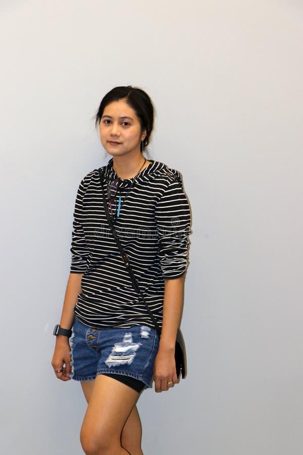 Mujer moderna asiática en blanco y color de las rayas negras de la camiseta de manga larga en fondo gris fotografía de archivo libre de regalías