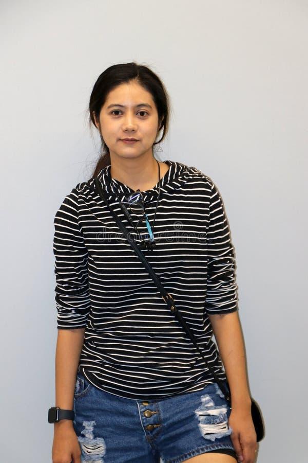 Mujer moderna asiática en blanco y color de las rayas negras de la camiseta de manga larga en fondo gris fotos de archivo libres de regalías