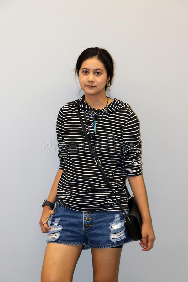 Mujer moderna asiática en blanco y color de las rayas negras de la camiseta de manga larga en fondo gris fotografía de archivo