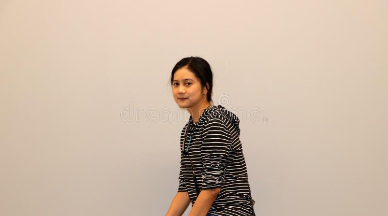 Mujer moderna asiática en el blanco y el color de la camiseta de manga larga, grados cumplidos 45 de las rayas negras imágenes de archivo libres de regalías