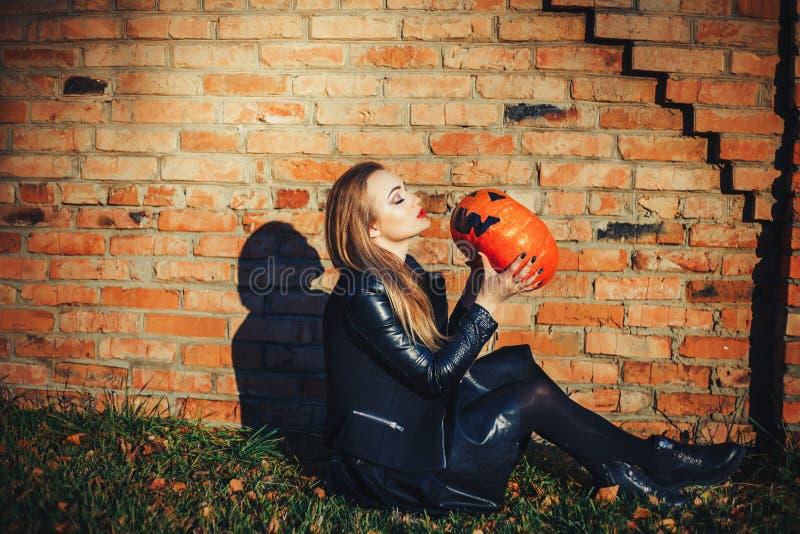 Mujer moderna de Halloween Calabaza atractiva 'truco o invitación 'de la tenencia de la bruja Preparación de la mujer en la chaqu foto de archivo