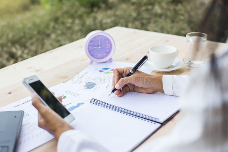 Mujer moderna del lugar de trabajo que usa el teléfono móvil que se sienta en la tabla de madera en oficina imágenes de archivo libres de regalías