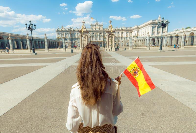 Mujer moderna del viajero con la bandera de España contra Royal Palace imagenes de archivo
