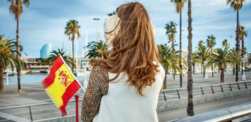 Mujer moderna en orejeras en Barcelona con la bandera española fotografía de archivo libre de regalías