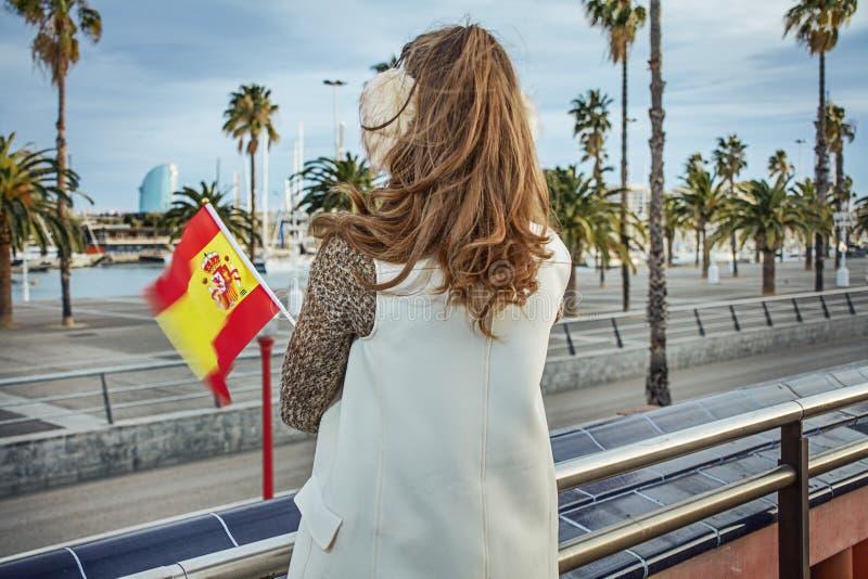 Mujer moderna en orejeras en Barcelona con la bandera española imagen de archivo