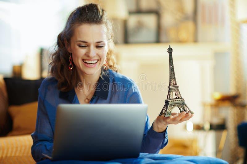 Mujer moderna feliz con el recuerdo de la torre Eiffel usando el ordenador port?til foto de archivo libre de regalías