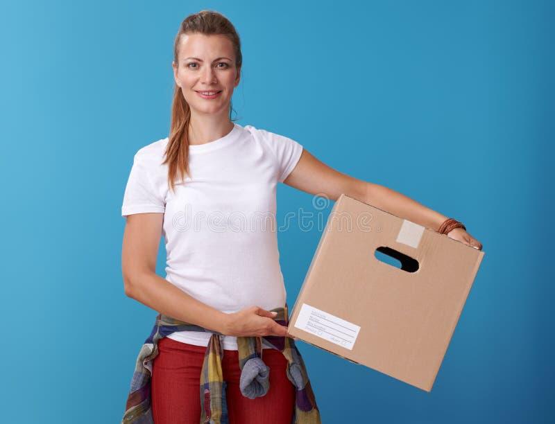 Mujer moderna feliz en la camisa blanca que sostiene la caja de cartón en azul imágenes de archivo libres de regalías