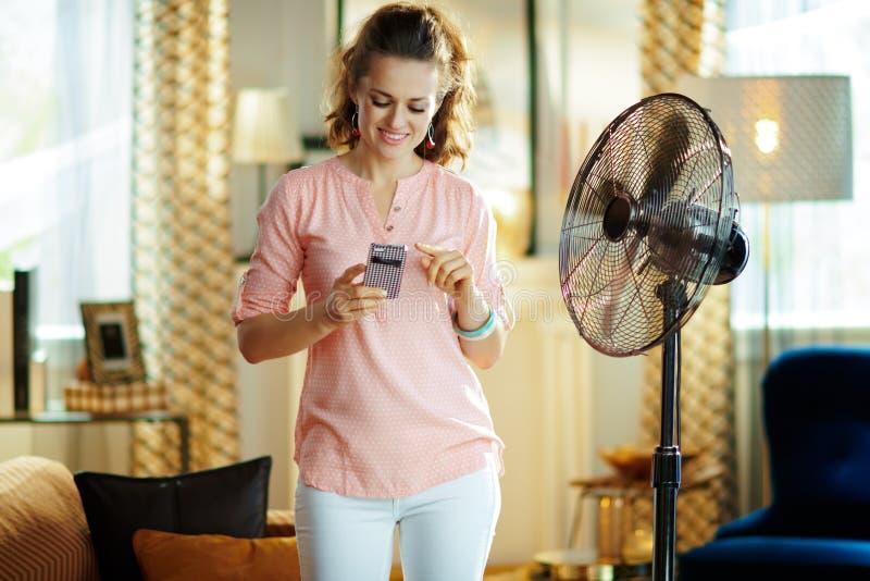 Mujer moderna feliz que usa el app casero elegante para controlar la fan imagenes de archivo