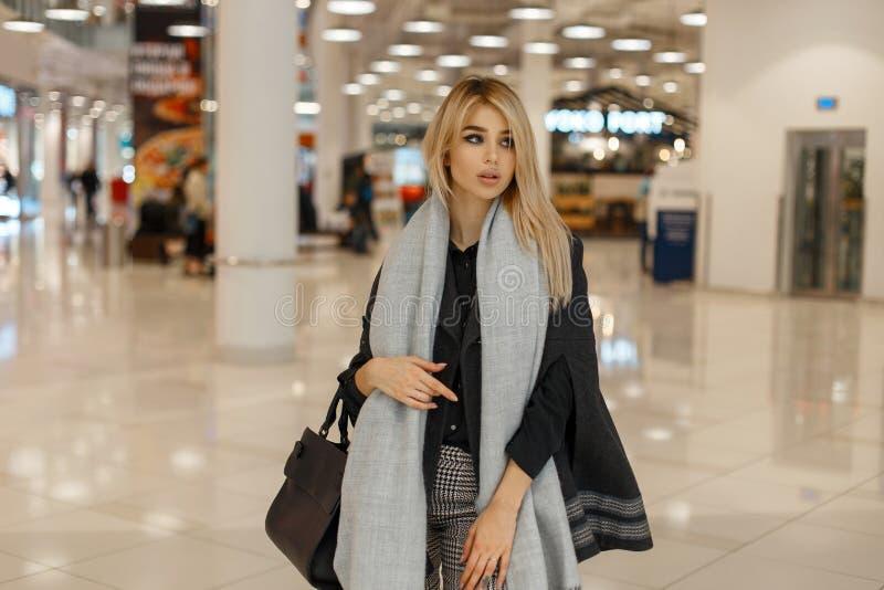 Mujer moderna joven elegante rubia en una capa elegante lujosa con una bufanda de moda gris del vintage foto de archivo