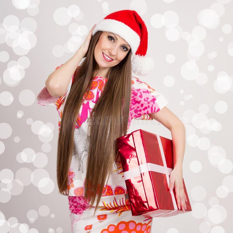 Mujer moderna joven linda de Papá Noel con la caja larga del pelo y de regalo imagen de archivo libre de regalías