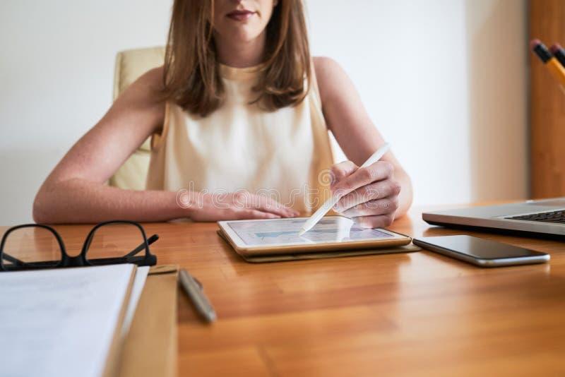 Mujer moderna que trabaja con la tableta en oficina imagen de archivo