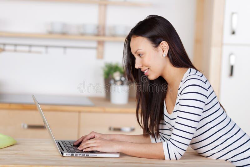 Mujer moderna que usa el ordenador portátil en su cocina fotografía de archivo libre de regalías