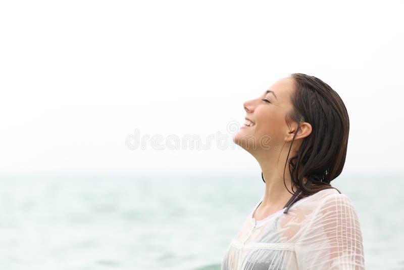 Mujer mojada que respira el aire fresco en la playa imagen de archivo