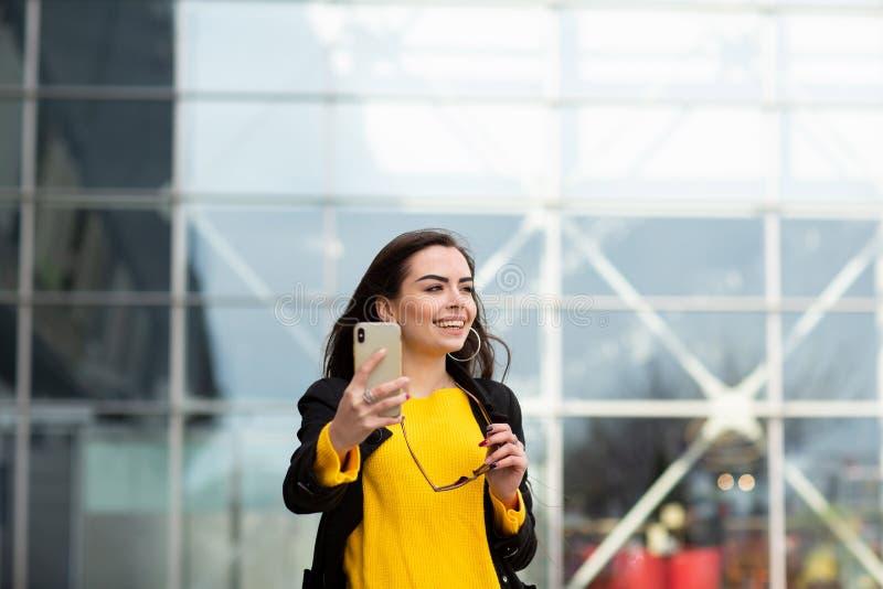 Mujer morena alegre en el su?ter amarillo que hace el sefie contra fondo del aeropuerto Tecnolog?a moderna fotografía de archivo