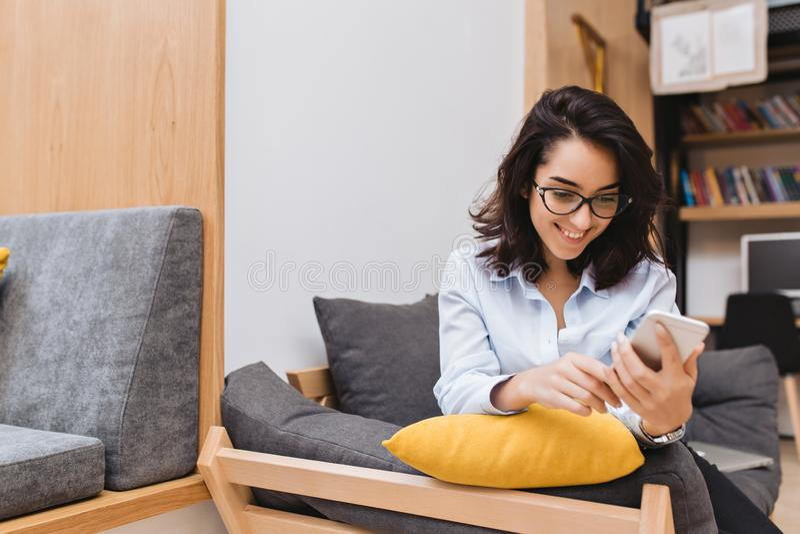 Mujer morena alegre joven del retrato en los vidrios negros que se enfrían en el sofá en el apartamento moderno Usando el teléfon imagen de archivo