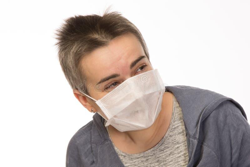 mujer morena atractiva blanca del primer con el pelo corto que lleva una máscara durante una epidemia de la gripe Aislado foto de archivo