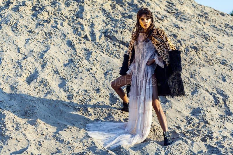 Mujer morena atractiva en cubierta larga de la playa translúcida para arriba con el abrigo de pieles del leopardo que presenta en imagen de archivo libre de regalías