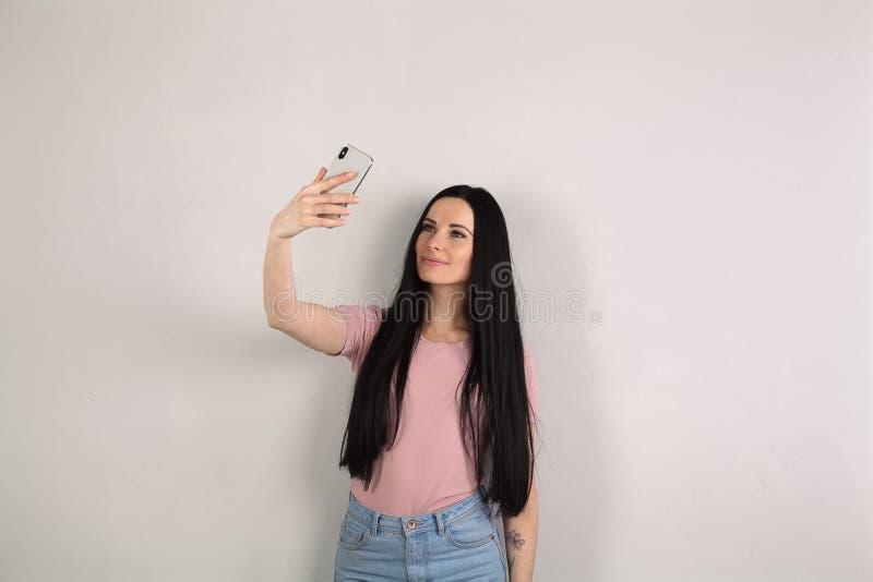 Mujer morena atractiva joven con el pelo largo que hace una pausa los tejanos que llevan del fondo gris y la tenencia rosada de l foto de archivo