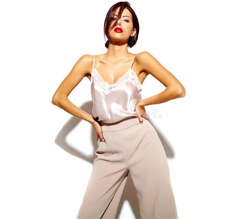 Mujer morena atractiva linda feliz hermosa con los labios rojos en ropa interior de los pijamas en el fondo blanco foto de archivo libre de regalías