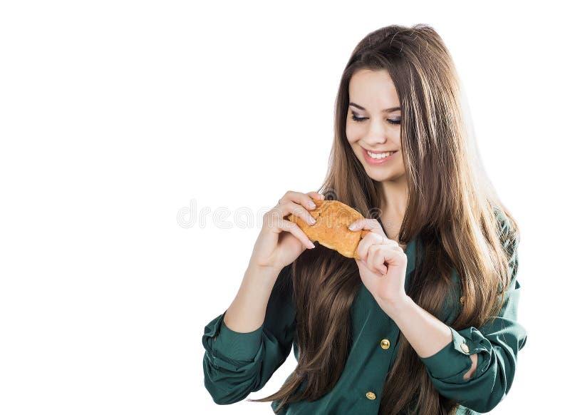 Mujer morena atractiva que come un cruasán en fondo aislado imagen de archivo libre de regalías
