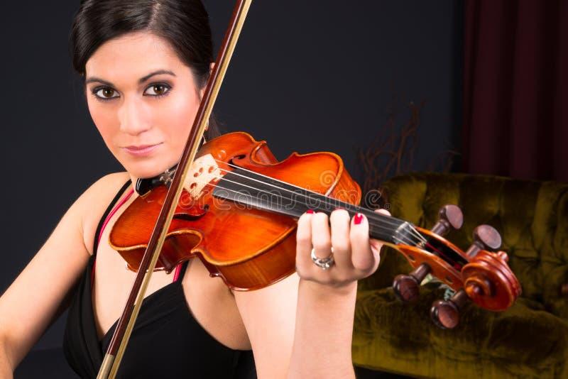 Mujer morena atractiva sensual que juega secuencias acústicas del concierto fotografía de archivo
