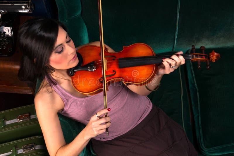 Mujer morena atractiva sensual que juega secuencias acústicas del concierto foto de archivo libre de regalías