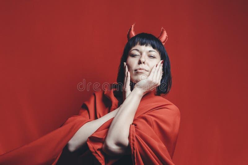 Mujer morena bonita con los cuernos del diablo rojo imágenes de archivo libres de regalías