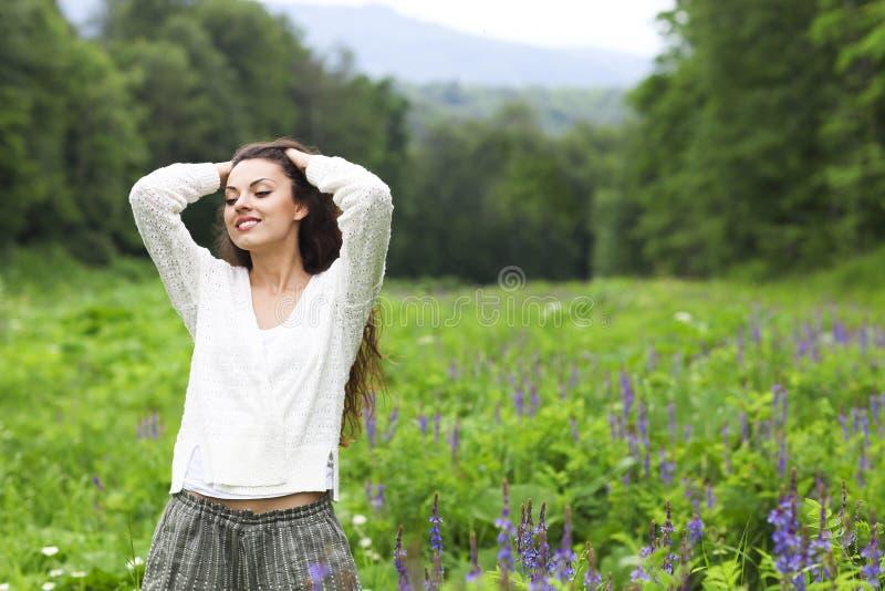 Mujer morena bonita feliz en campo de flor fotografía de archivo libre de regalías