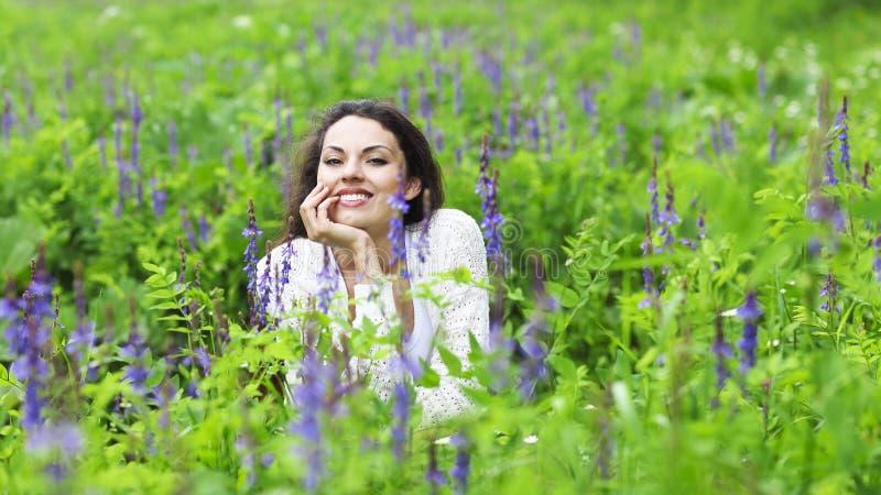 Mujer morena bonita feliz en campo de flor imágenes de archivo libres de regalías