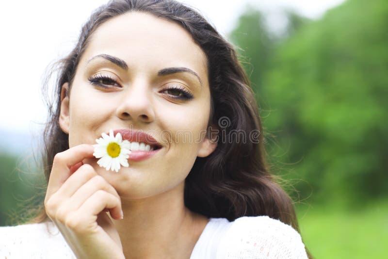 Mujer morena bonita feliz en campo de la manzanilla fotos de archivo