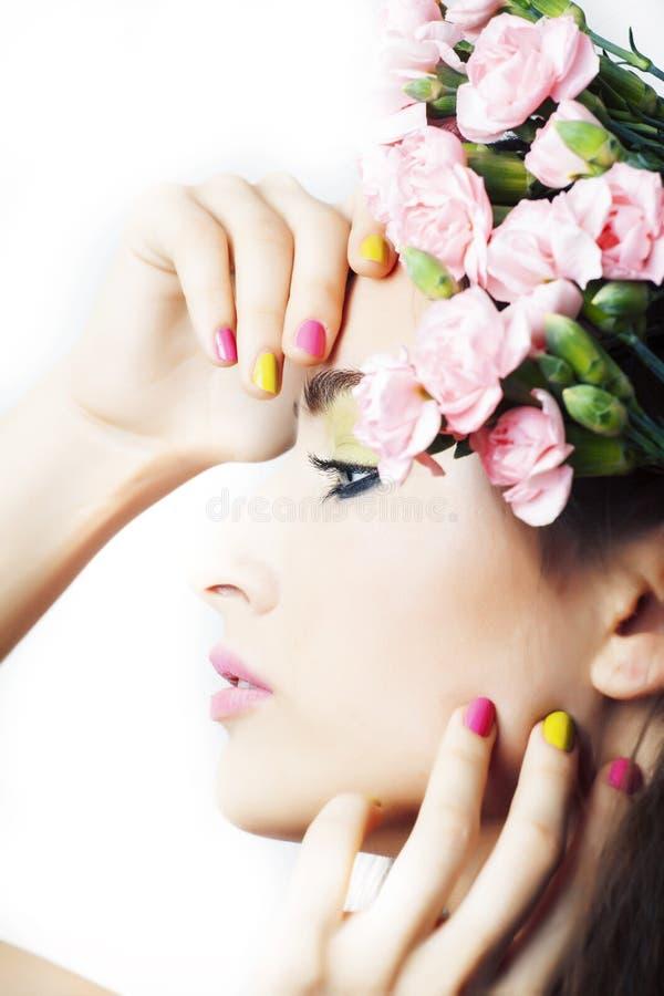 Mujer morena bonita joven con las flores rosadas y la manicura que presentan alegre aislada en el primer blanco del fondo foto de archivo libre de regalías