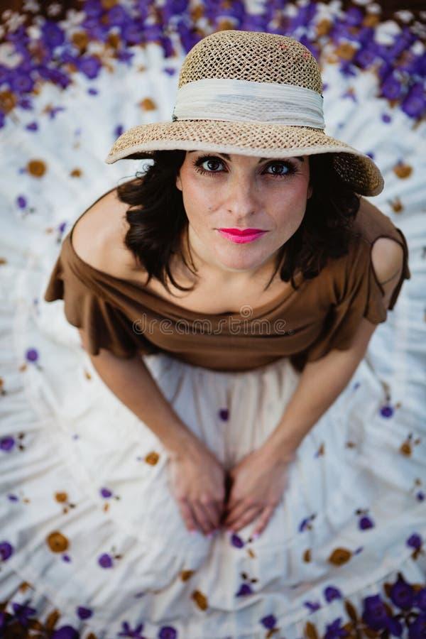 Mujer morena bonita que se sienta con una falda florecida Visión desde a foto de archivo