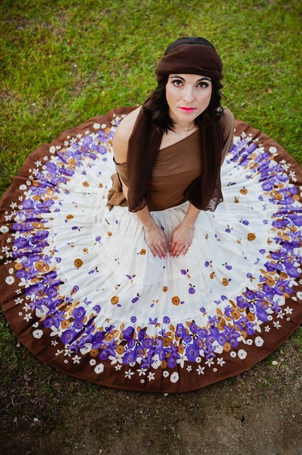 Mujer morena bonita que se sienta con una falda florecida Visión desde a imágenes de archivo libres de regalías
