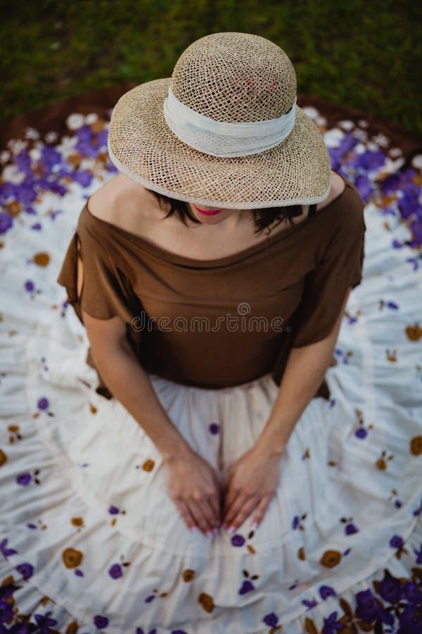 Mujer morena bonita que se sienta con una falda florecida Visión desde a imagen de archivo libre de regalías