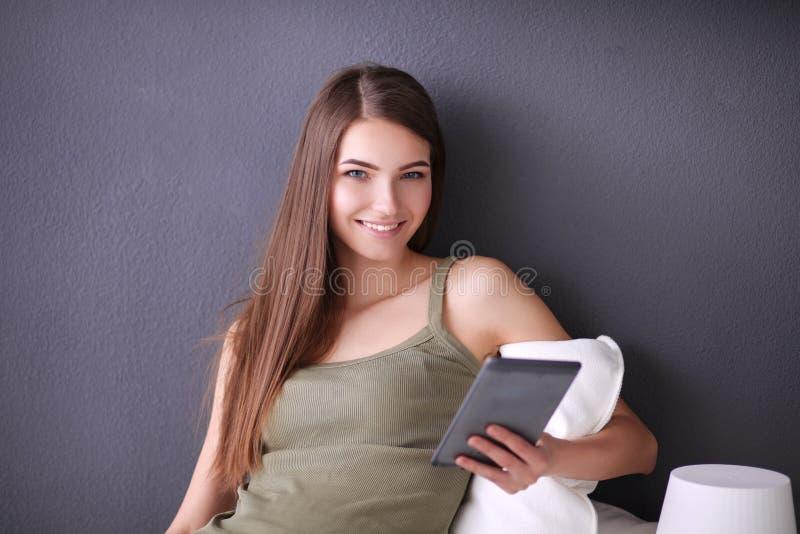 Mujer morena bonita que se sienta en el piso con una almohada y una tabla plana imágenes de archivo libres de regalías