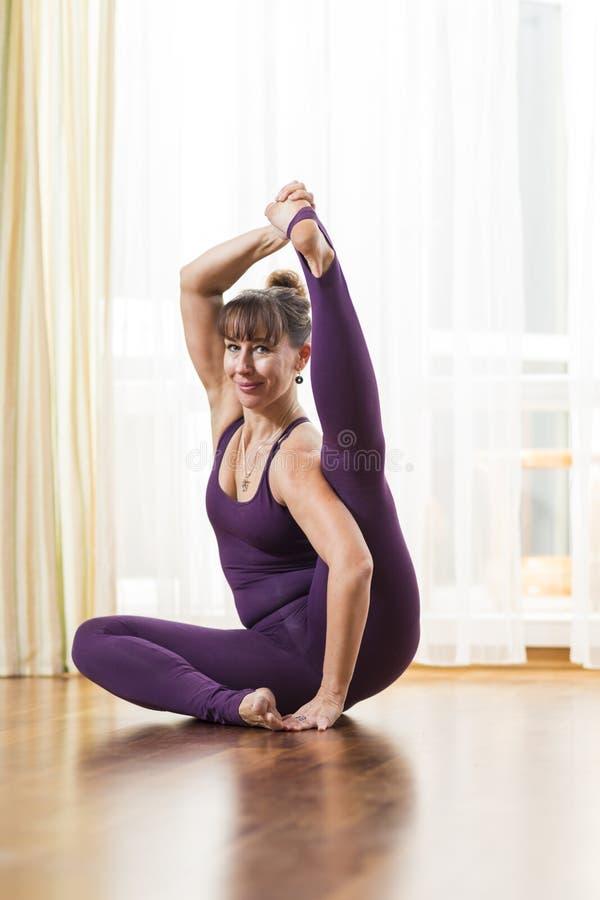 Mujer morena caucásica deportiva en buena yoga practicante apta dentro delante de Sunny Window grande El hacer estirando ejercici fotos de archivo libres de regalías