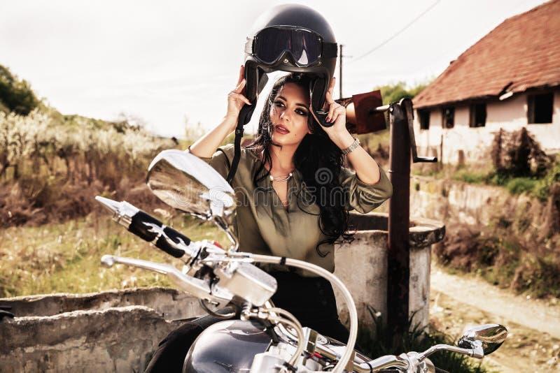 Mujer morena de la motocicleta hermosa con una motocicleta clásica c fotografía de archivo