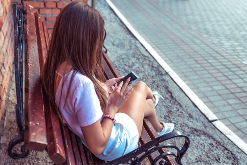 Mujer morena de la muchacha hermosa que se sienta en un banco de parque Vídeo de observación en el texto de las impresiones del t imagen de archivo