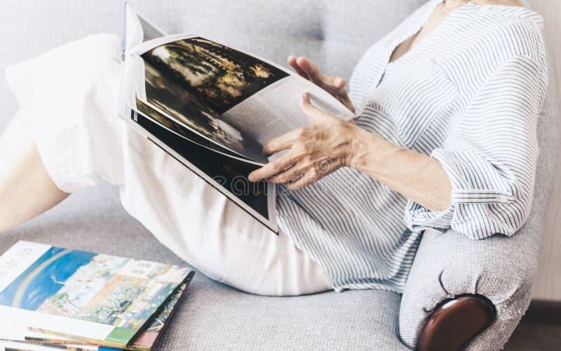 Mujer morena de mediana edad en el sof? gris que mira el ?lbum con las pinturas de los artistas fotos de archivo libres de regalías