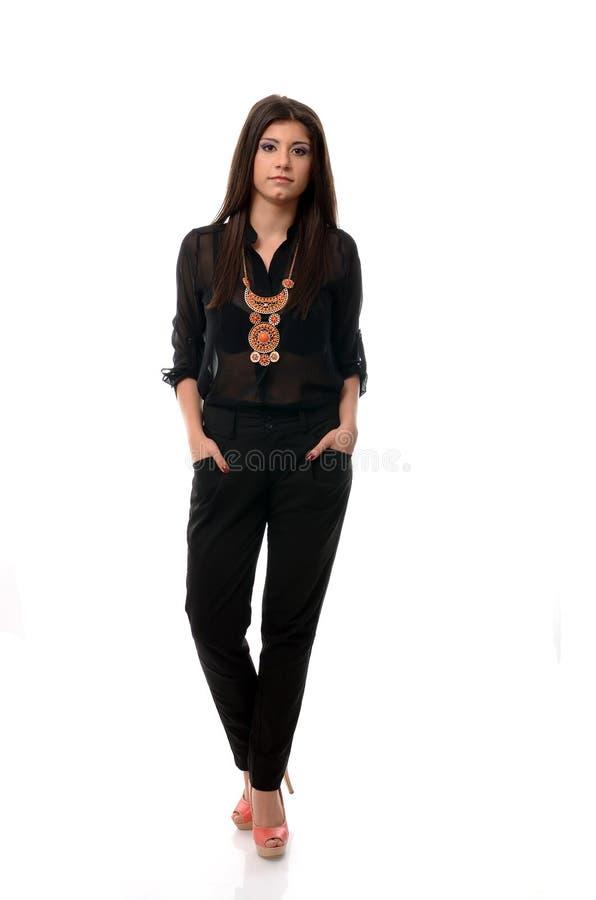 Mujer morena de moda que presenta con las manos en bolsillos, foto de archivo