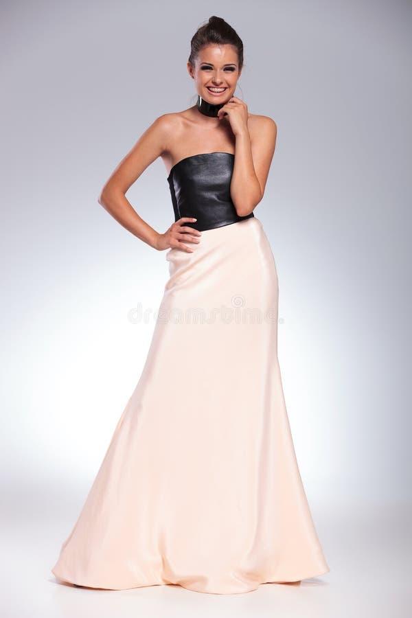 Mujer morena de risa joven en un vestido de noche largo imagen de archivo