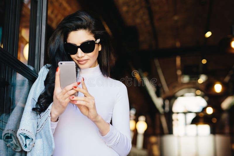 Mujer morena elegante con la piel pura, gafas de sol que llevan, havin fotos de archivo