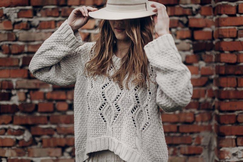 Mujer morena elegante en el posin blanco blanco del sombrero y del suéter del boho imágenes de archivo libres de regalías