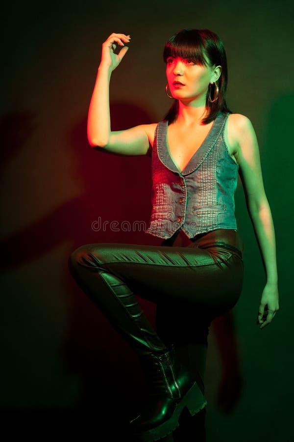 fe562566dbf0 Mujer morena elegante en los pantalones de cuero en luz roja y verde  fotografía de archivo