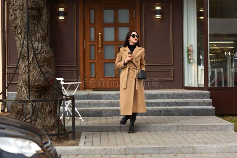 Mujer morena elegante joven hermosa que lleva la capa beige larga, la camisa negra y los zapatos, caminando a lo largo de las cal imagenes de archivo
