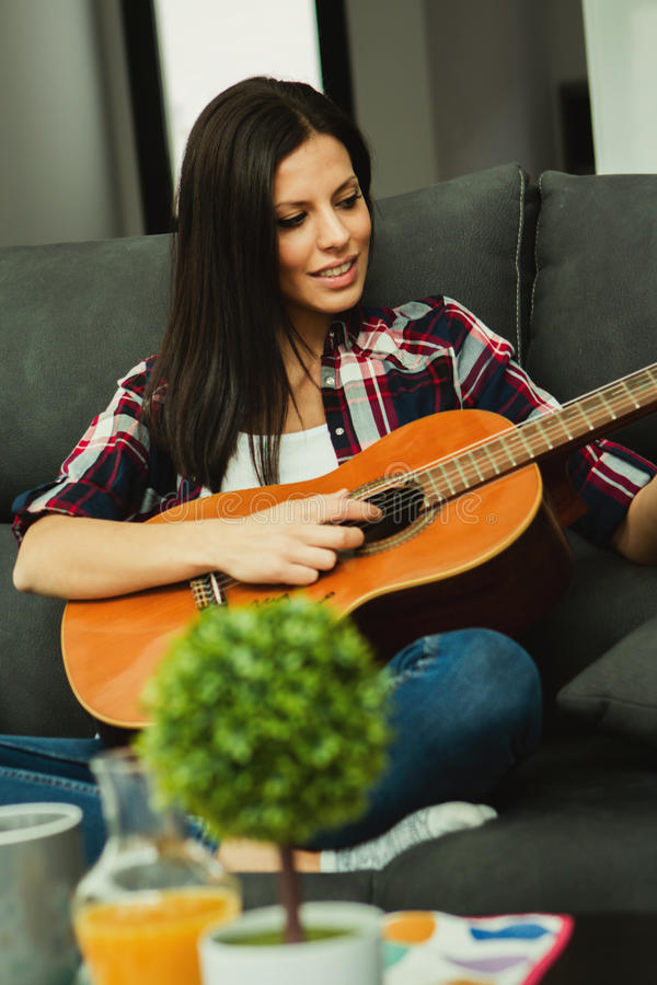 Mujer morena en casa que toca la guitarra fotos de archivo