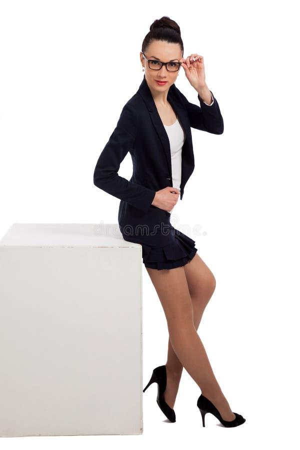 Mujer morena en falda negra y la chaqueta que se sientan en el cubo fotos de archivo